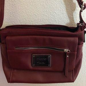 Nicole Miller small shoulder handbag in burgundy.